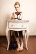 Vintage style. Barefoot girl sitting at retro desk