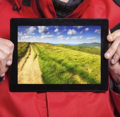 Man showing mountains on tablet. Travel