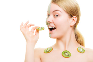 Skin care. Woman in clay mask on face and kiwi