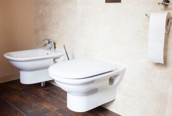 Hygiene. White porcelain bidet and toilet. Interior of bathroom.