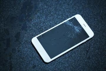 Broken iPhone on asphalt outdoors