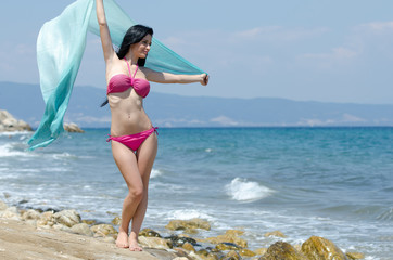 Playful girl in a transparent fabric stands on a sea beach