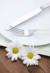 Cutlery on plate with flowers on wooden table