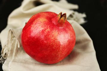 Juicy ripe pomegranates on tablecloth