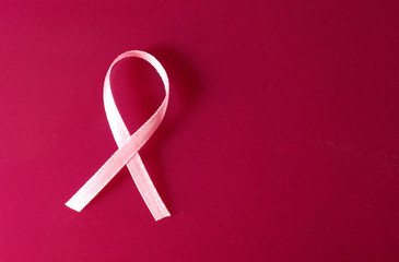 Pink breast cancer ribbon on pink background