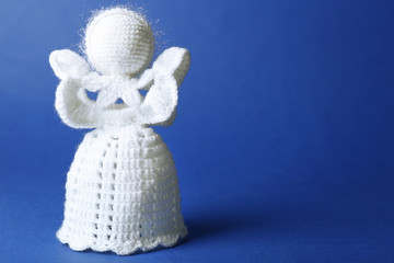 Knitted Christmas angel on color background