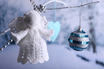 Knitted Christmas angel hanging on bud on light background