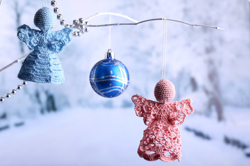 Knitted Christmas angels hanging on bud on light background