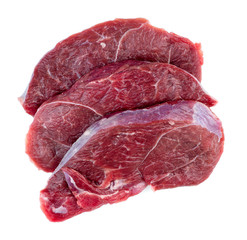 Aerial of raw red meat steaks isolated against a white backgroun