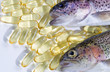 Fish oil capsules with fresh fish on white background - 74698677