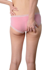 Slim woman checking her fat and cellulite on buttocks isolated o