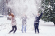Three teenage girls throwing snow in the air on beautiful winter