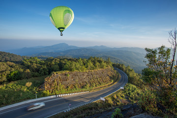 Hot air balloon over high mountain and road