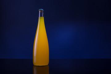 bottle of orange juice on a dark background