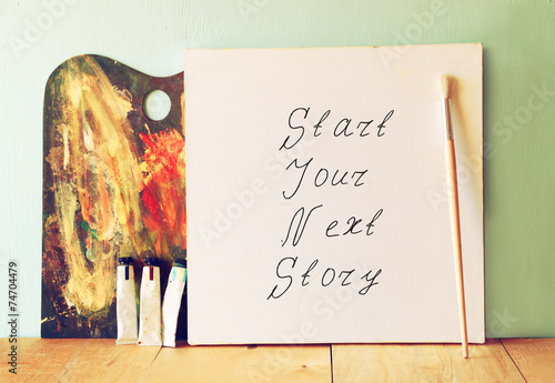 canvas with the phrase start your next story next to oil paints  - 74704479