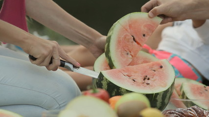 Close up of how mom cut watermelon in nature during a family