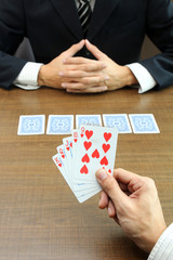 Business gamble with focus on hand holding cards