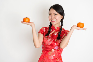 Asian chinese girl holding tangerine orange