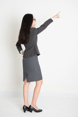 Full body backside Asian business woman pointing