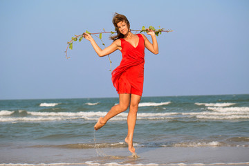 Young redhead girl in red dress jumping at the beach.