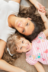 Mother and little daughter lying together on the floor