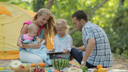 Happy family consisting of four sitting on a picnic, showing