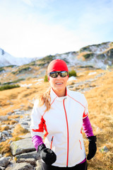 Happy woman running in mountains on winter fall sunny day