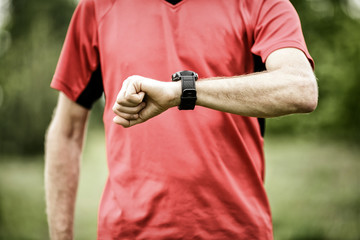 Runner looking at sport or smart watch checking pulse or gps