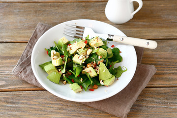 Salad with avocado, spinach and nuts in a white bowl