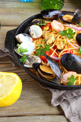 Pasta with mussels, squid and parsley in a frying pan