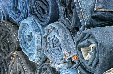 Stack of rolled colored jeans. Side view
