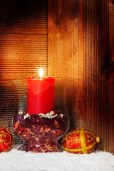Kerze vor Holz im Schnee