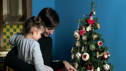 Happy mom and child, mother and baby looking at Christmas tree