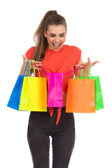 Surprised girl with colorful shopping bags