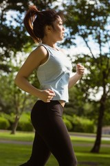 Side view of healthy woman jogging in park