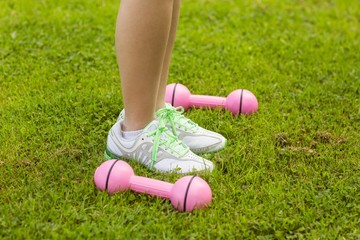 Woman with dumbbells on grass at park