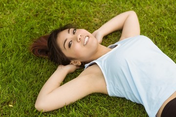 Healthy and beautiful woman lying on grass in park