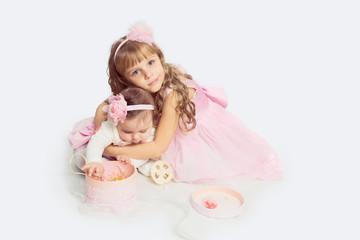 Adorable little sister hugging her baby sister