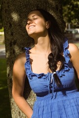 Brunette leaning against a tree enjoying the sunshine