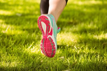 Woman in running shoes running on grass