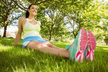 Happy brunette in sportswear relaxing on the grass