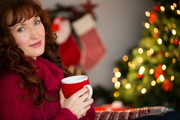 Pretty redhead holding mug of hot drink