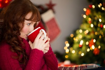 Beautiful redhead drinking hot drink at christmas