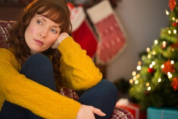 Beauty red hair thinking on the armchair at christmas