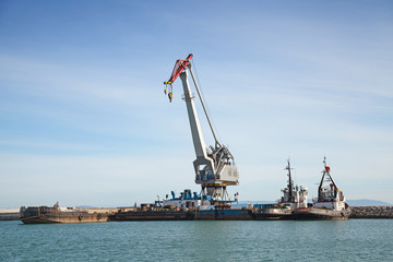 Floating crane and tug boats stand moored in port