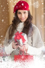 Smiling brunette holding gift and shopping bag
