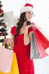 Composite image of brunette in red dress holding shopping bags