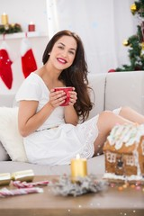 Composite image of smiling brunette holding a mug of hot drink