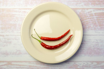 White round plate with two red peppers