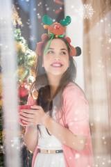 Composite image of smiling brunette in christmas hat holding mug
